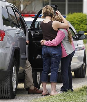 A cousin, left, mourns with the girlfriend of James Safadi, 34, as authorities investigate his shooting death in his home.
