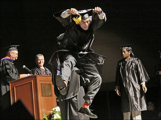 Lourdes Zander Epps Zander Epps of San Diego jumps as he crosses the stage to receive his bachelor's degree in interdisciplinary studies during Lourdes University's commencement ceremony.