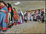 Pakistani women line up to cast ballots during a repolling for the general elections in a Karachi district. The shooting death of a party co-founder kept many home.