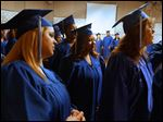 Phylicia Cattladge of South Toledo, center, waits with her fellow graduates backstage before the start of the commencement ceremony for students in the Adult Basic and Literacy Education program today at the Center for Fine and Performing Arts at Owens Community College in Perrysburg Township.