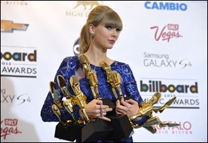 "Taylor Swift poses backstage with her awards at the Billboard Music Awards at the MGM Grand Garden Arena on Sunday in Las Vegas. Swift won eight of 11 awards, including top artist and top Billboard 200 album for ""Red."" She told the crowd: ""You are the longest and best relationship I ever had."""