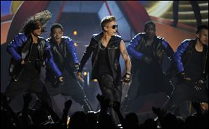 Justin Bieber, center, performs at the Billboard Music Award. Bieber also performed — twice — and was also a multiple winner with three awards, including top male artist, social artist and the fan-voted milestone award, beating out Swift and Bruno Mars.