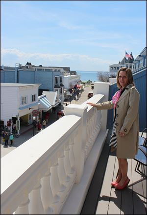Melanie Libby stands on a balcony at the Bicycle Street Inn. She and Ira Green want to demolish a former fudge shop to build two more hotels on Mackinac Island.