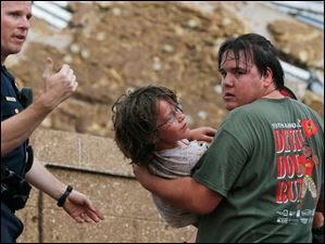 A child is carried from the rubble of the Plaza Towers Elementary School.