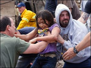 A child is passed along a human chain of people after being pulled from the rubble.