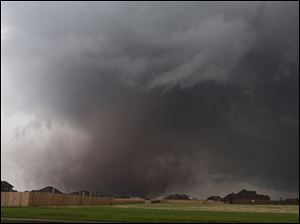 The tornado moves past homes in Moore.