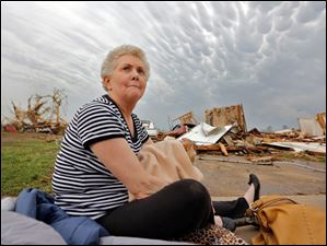 Kay James holds her cat as she sits in her driveway after her home was destroyed.