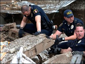 Moore police dig through the rubble of the Plaza Towers Elementary School.