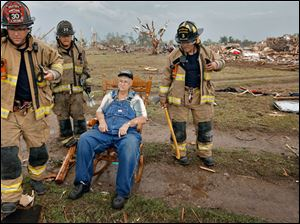Oklahoma City firefighters check on the status of Gene Tripp as he sits in his rocking chair where his home once stood after being destroyed.