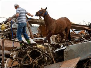 Rescuers recover a horse from the remains of a day care center and destroyed barns.