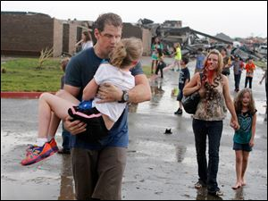 Teachers carry children away from Briarwood Elementary school after a tornado destroyed the school.