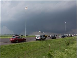 The tornado that moved through Moore as seen from side of the road in the distance.