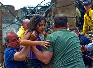A child is pulled from the rubble of the Plaza Towers Elementary School in Moore, Okla., and passed along to rescuers.