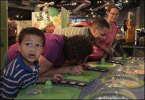 Jorge Aguilar, 6, left, his grandmother Nedra Pike, and parents Ryan Pike and Whitney Mekus react to Sniff Sniff U Stink, an interactive exhibit at Grossology. Each member of the Defiance family took a whiff of something from the human body at the Imagination Station in downtown Toledo on Sunday.