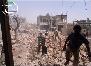 A citizen journalism image provided by Qusair Lens shows Syrians inspecting the rubble of damaged buildings due to government airstrikes, in Qusair, Homs province, Syria.