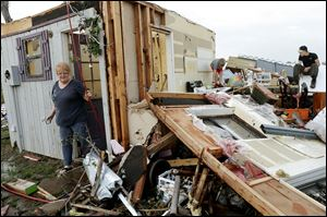 Marlena Hodson walks out of her home as her grandsons, Campbell Miller, 10, and Dillon Miller, 13, at right, help her sort through belongings after a tornado damaged her home Carney Okla., on Sunday.