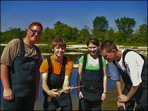 Alex Kocher (Bowsher) holds a longnose gar that he and fellow Wildlife Management students Will Gilbert III (Waite), left, Leigha Kelley (Waite), and Tres' Black (Start) netted during field work on the Maumee River.