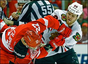 Detroit defenseman Kyle Quincey, left, and Chicago left wing Bryan Bickell mix it up in the first period.