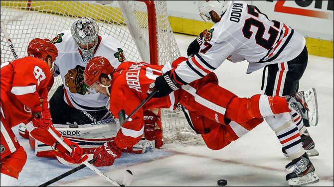Chicago's Johnny Oduya checks Detroit's Justin Abdelkader in front of goaltender Corey Crawford in Monday night's game.
