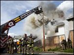 Firefighters from the Toledo Fire Department battle a fully involved structure fire Oak Street. The fire is being investigated as a possible arson.