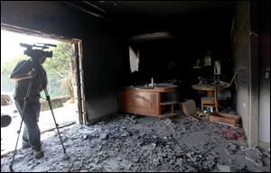 A cameraman films one of  U.S. consulate burnt out offices after an attack that killed four Americans, including Ambassador Chris Stevens on the night of Tuesday, Sept. 11, 2012, in Benghazi, Libya.