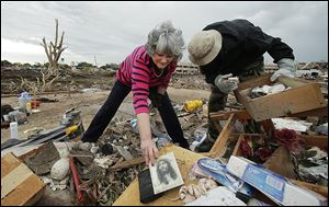 Lea Bessinger salvages a picture of Jesus as she and her son, Josh Bessinger, sort through the rubble of Ms. Bessinger's home in Moore, Okla. Some residents returned Tuesday to assess the damage.