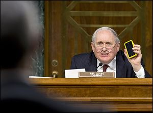 Sen. Carl Levin (D., Mich.) holds up his Apple iPhone while questioning Apple CEO Tim Cook about methods used by corporations to shift profits offshore.