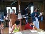 Volunteers of Sylvania's Historical Village, Connie Ryan, left, and Sarah Groves, right, hold up posters and advertisements published in the 1850's by slave owners asking for the prompt return of a runaway slave. Fifth grade students of Sylvan Elementary had an all day field trip at the village about the underground railroad.