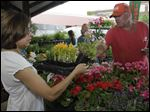 Martha Bradley of Toledo buys flowers from Andy Keil, of Andy Keil Greenhouse in Swanton, at last year's Flower Day event at the Toledo Farmers' Market. The market is at Superior and Market streets, on the south end of downtown.