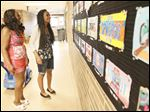Myra Beyene, right, shows her mother, Zebib Beyene Gradina her award-winning art work during an art fair at McCord Junior High.