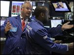 In this Aug. 11, 2010 photo, specialist John Urbanowicz, left, talks with a colleague on the floor of the New York Stock Exchange. Stocks are opening Wednesday, May 22, 2013, slightly higher as investors watch for the latest moves from the Federal Reserve.  (AP Photo/Richard Drew)