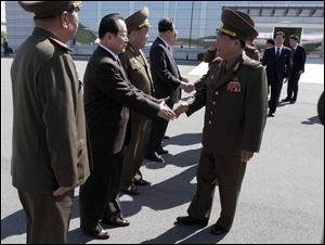 High-ranking North Korean party and military official Choe Ryong Hae, front right, shakes hands with officials as he departs for China as a special envoy of North Korean leader Kim Jong Un, at Pyongyang airport, North Korea today.