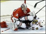Chicago Blackhawks center Jonathan Toews crashes into Detroit goalie Jimmy Howard during the second period. Howard kept everything out of the night on Thursday night to give the Wings a commanding lead as the series heads back to Chicago.