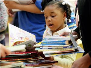 Samere Harton, 6, chooses a book from a llarge stack of books during a party to celebrate the end of a successful first year of WordShop, a creative writing program developed by the Women's Initiative of United Way,  at  Rosary Cathedral School on May 23, 2013.