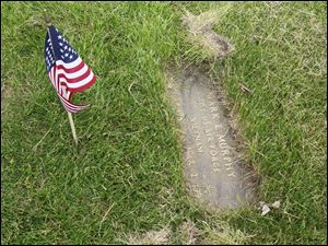 The grave marker of Sgt. Mark E. Murphy, USAF, after being cleaned and given a flag by the volunteers. Vietnam veteran Izzy Ortiz, a graduate of Whitmer H.S. who served in the Marine Corps, organized the effort in 1989, and has continued to coordinate it since that time.