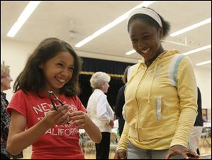 Angelica Torres, 11, left, and LaNia Sanders, 11, right, choose free books to take home.