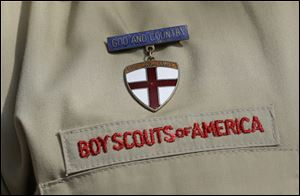 A close up detail of a Boy Scout uniform worn by Brad Hankins, a campaign director for Scouts for Equality, as he responds questions during a news conference in front of the Boy Scouts of America headquarters in Irving, Texas.
