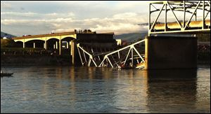 People look on after the Interstate 5 bridge collapsed over the Skagit River in Mount Vernon, Wash.