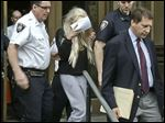 Actress Amanda Bynes, center, wearing sweats and a blonde wig, shields her face as she is escorted after a Manhattan criminal court appearance.
