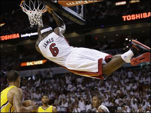 Miami Heat forward LeBron James (6) hangs from the basket after dunking the ball during the second half.