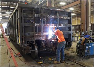 John Spurlock welds on a  railcar at The Andersons' railcar-repair facility in Maumee. The Ander­sons' rev­e­nues rose sig­nifi­cantly in 2012 to $5.3 bil­lion from $4.6 bil­lion in 2011. Fueling that rise was the growth in its grain, ethanol, and plant-nutrient divisions.