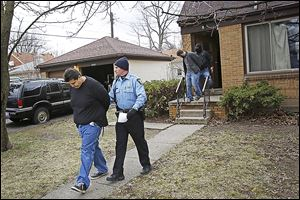 Adam Michalak, left, and Joshua Bennett, right, are led out of a South Toledo home by police after a Toledo police raid in April.