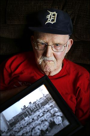 Ken Silverthorne, 93, holds a Mud Hens team photo from the 1930s, one of his prized possessions.