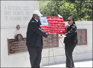 Toledo Mayor Mike Bell and City Council President Paula Hicks-Hudson place a floral flag during the city's Memorial Day ceremony that also featured bagpipes.