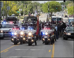 Toledo Police Department motorcycles lead the city's Memorial Day parade, which at times proved to be a loud procession of marching bands, military vehicles, clowns, and candy throwers.