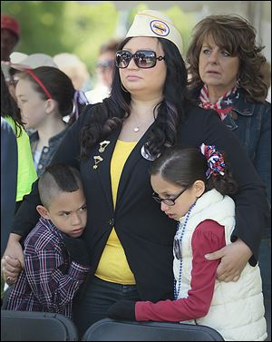 Veronica Mora, a Gold Star Wife, holds her son, Topher, 7, and daughter Celina, 9, at Toledo's Memorial Day ceremony that followed Saturday's parade.
