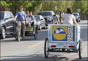 Maxwell Austin, owner of Glass City Pedicabs, gives passenger Matt Rowland a ride while he passes employee Brittany Ryan, right, on the street.