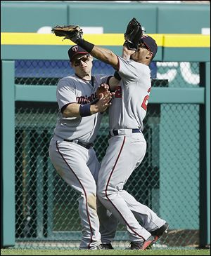 The Twins' Wilkin Ramirez, right, and Josh Willingham collide after chasing a fly ball hit by the Tigers' Omar Infante in the sixth inning. Ramirez was injured on the play, but hung on to make the out.