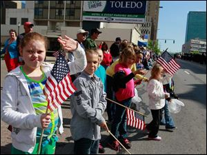 Brittnie Childress, 9, of Toledo, waves after the Springfield H.S. band passed.