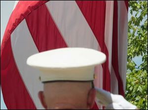 Marine Sgt. Steven Kosinski salutes as the flag is raised at the beginning of the memorial service.